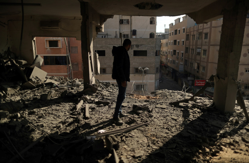 A Palestinian man inspects a building destroyed in Israeli air strikes, in Gaza City May 5, 2019 (photo credit: SUHAIB SALEM / REUTERS)