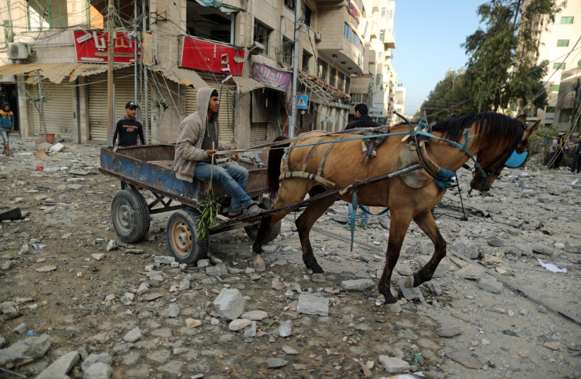A Palestinian rides a horse-drawn cart through a debris-strewn street near a building destroyed by Israeli air strikes, in Gaza City May 5, 2019 (photo credit: SUHAIB SALEM / REUTERS)