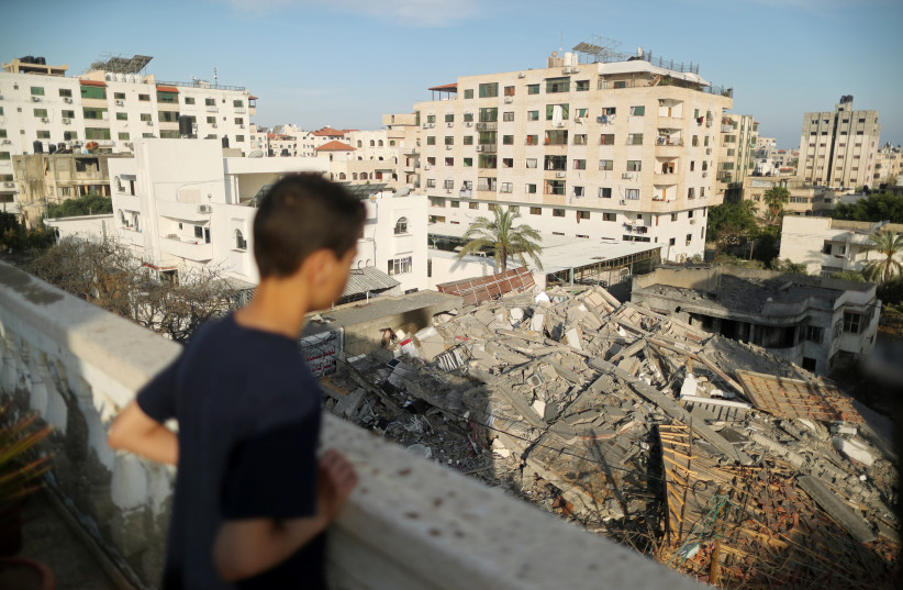 A Palestinian boy looks at the remains of a building that was destroyed in Israeli air strikes, in Gaza City May 5, 2019 (photo credit: SUHAIB SALEM / REUTERS)