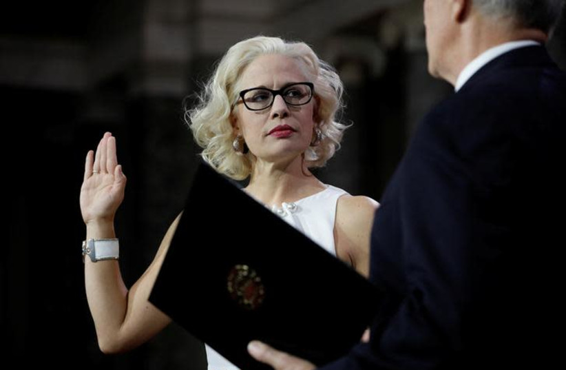 Sen. Kyrsten Sinema (D-AZ) participates in a mock swearing in with U.S. Vice President Mike Pence during the opening day of the 116th Congress on Capitol Hill in Washington (photo credit: REUTERS/AARON P. BERNSTEIN)