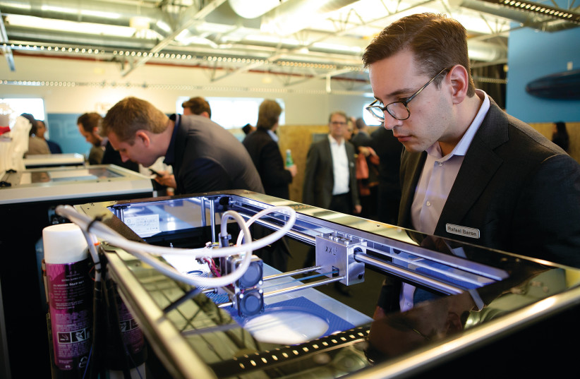 A MAN watches a 3D Printer in action while attending a conference.  (photo credit: TRINITY WHEELER PHOTOGRAPHY)