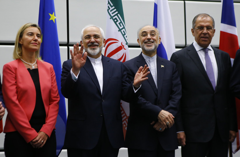 Iran FM Zarif, EU Rep. for Foreign Affairs Mogherini, and Iranian and Russian officials at signing of nuclear deal in Vienna, 2015 (photo credit: LEONHARD FOEGER / REUTERS)