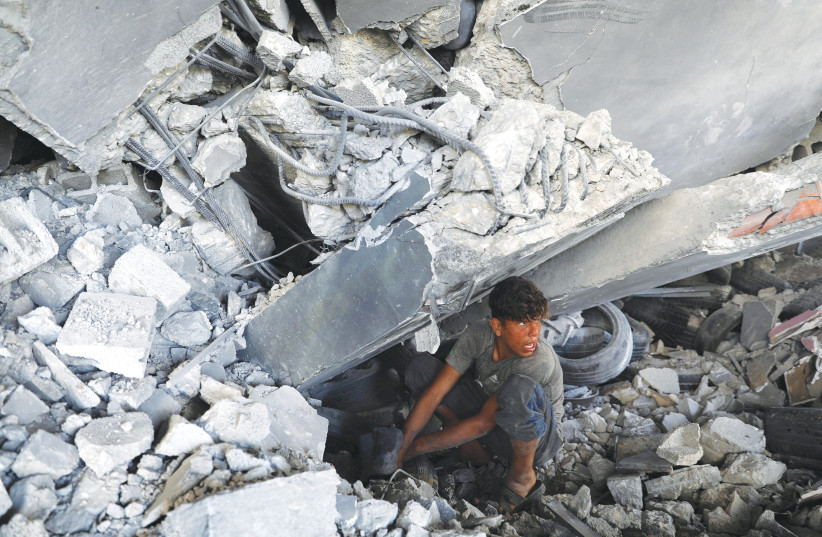 A GAZA CITY resident searches for his belongings under the rubble of a building that was destroyed during air strikes by Israel. (photo credit: MOHAMMED SALEM/REUTERS)