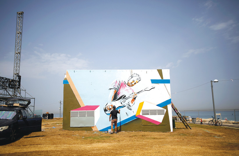 A MAN PAINTS a mural on a structure located close to the Eurovision Village in Tel Aviv (photo credit: REUTERS/CORINNA KERN)