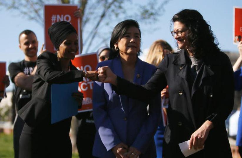 Rep. Ilhan Omar (D-MN) shares a fist bump with Rep. Rashida Tlaib (D-MI) (photo credit: REUTERS/JIM BOURG)