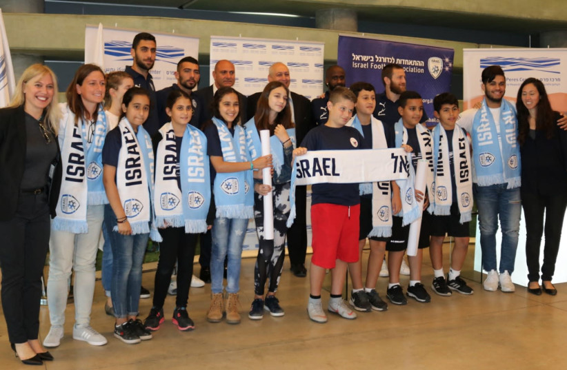 Israeli soccer players join school children from Jaffa at the Peres Center for Peace and Innovation (photo credit: Courtesy)