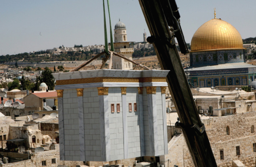 A model of the Temple is lowered by crane onto the roof of the Aish HaTorah Yeshiva in the Jewish Quarter in 2009 (photo credit: GALI TIBBON)