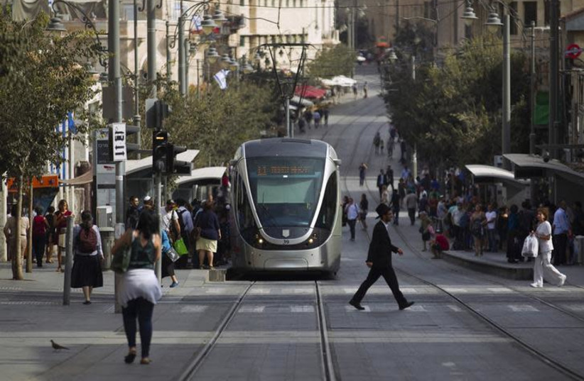 People walk near the light rail in the centre of Jerusalem (photo credit: REUTERS/AMIR COHEN)