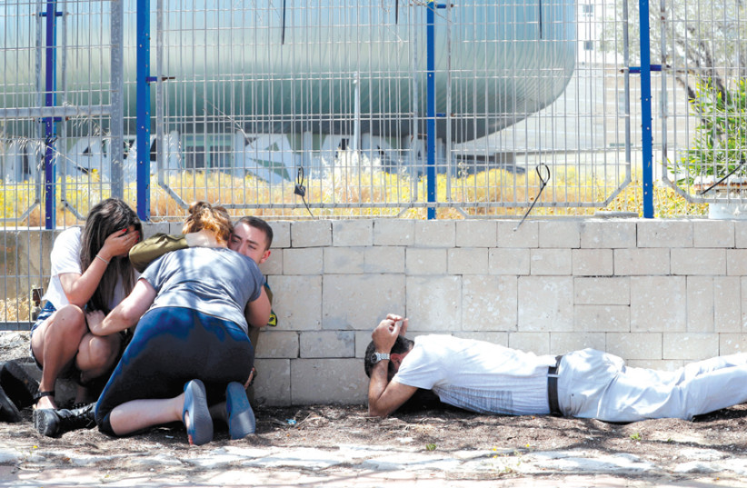 PEOPLE TAKE cover as they hear sirens warning of incoming rockets from Gaza, in Ashkelon on May 5. (photo credit: REUTERS)