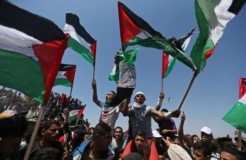 Demonstrators hold Palestinian flags during a protest marking the 71st anniversary of the 'Nakba', or catastrophe, when hundreds of thousands fled or were forced from their homes in the war surrounding Israel's independence in 1948, near the Israel-Gaza border fence, in the southern Gaza Strip May 1 (photo credit: IBRAHEEM ABU MUSTAFA / REUTERS)