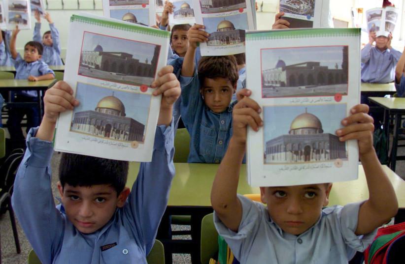 Palestinian kids display their textbooks (photo credit: AHMED JADALLAH / REUTERS)