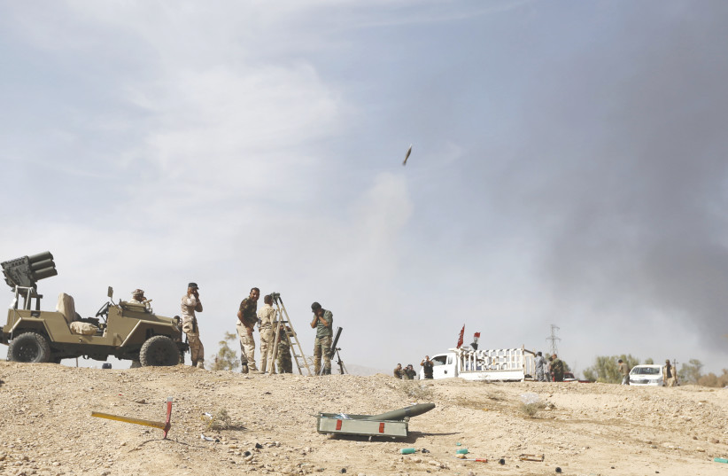 SHI'ITE FIGHTERS launch a mortar round toward Islamic State lines in al-Fatha, northeast of Baiji, in 2015. Iraqi forces, backed by Shi'ite militia fighters, say they have retaken a mountain palace complex of former president Saddam Hussein from Islamic State fighters, as government forces push ahea (photo credit: THAIER AL-SUDANI/REUTERS)