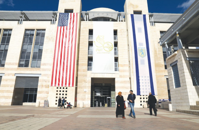 PEOPLE WALK at Jerusalem's City Hall as the American and Jerusalem flags hang on the municipality building in 2017. (photo credit: AMMAR AWAD / REUTERS)