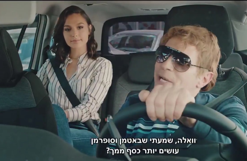 Gal Gadot sits in the back of a cab with driver Yuval Semo in her Eurovision video appearance (photo credit: SCREENSHOT/KAN)