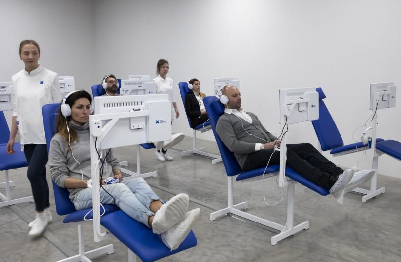 Visitors watching video-art films shown at 'Field Hospital' representing Israel in the Venice Bienalle  (photo credit: ELAD SARIG)