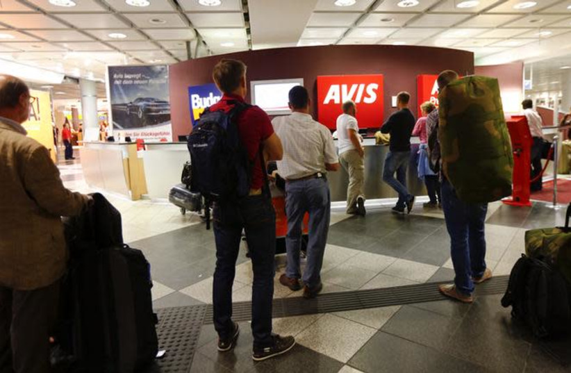 People queue at rental car desks at the international airport in Munich (photo credit: REUTERS/MICHAEL DALDER)