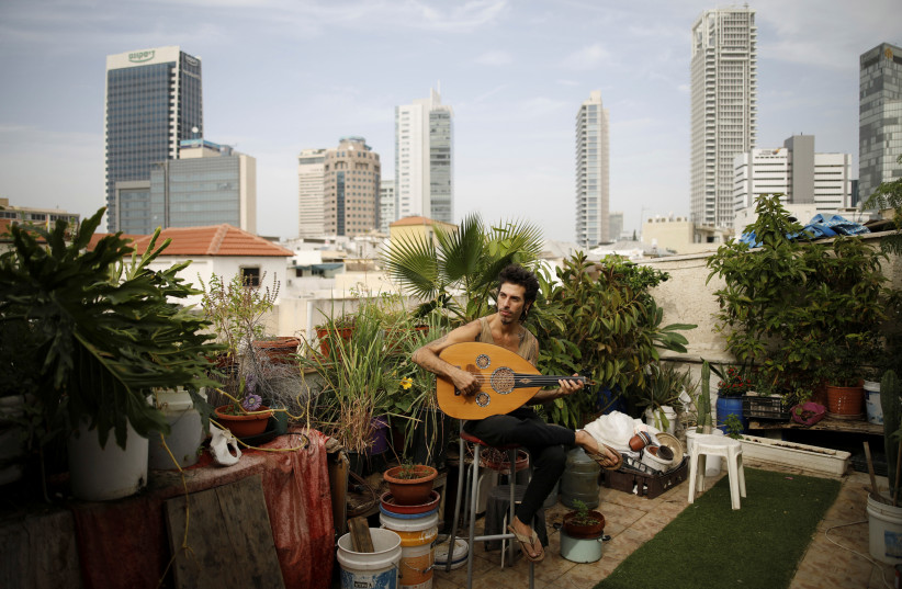 Musician Iyar Semel, 38, on his rooftop garden, where he grows herbs and vegetables, in Tel Aviv. Iyar planted an organic garden on his rooftop, with compost, vegetables, fruit trees and a shower, allowing him to merge his ecological lifestyle with the restraints of urban space. (photo credit: REUTERS/CORINNA KERN)