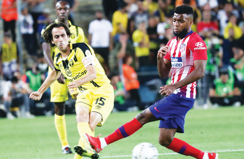 BEITAR JERUSALEM midfielder Yossi Benayoun (left) shoots past Atletico Madrid' Thomas Lemar during last night's friendly between the clubs at Teddy Stadium in Jerusalem, where Beitar notched a surprising 2-1 victory. (photo credit: DANNY MARON)