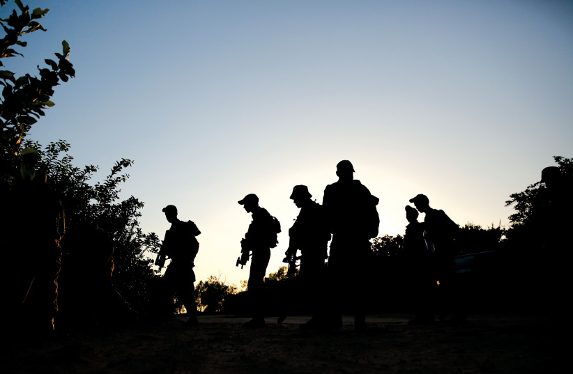 SOLDIERS WALK at night during a training mission.  (photo credit: REUTERS)