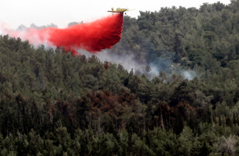A firefighting aircraft flies over a forest near kibbutz Harel which was damaged by wildfires during a record heatwave, in Israel May 24, 2019. (photo credit: RONEN ZVULUN / REUTERS)