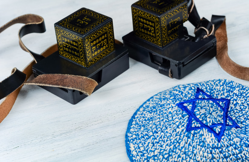 Pair of tefilin with black straps with blue kippah on white wooden background. (illustrative) (photo credit: INGIMAGE)