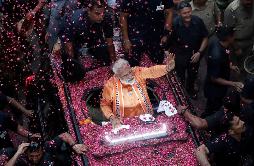 India's Prime Minister Narendra Modi waves towards his supporters during a roadshow in Varanasi, India (photo credit: ADNAN ABIDI/ REUTERS)