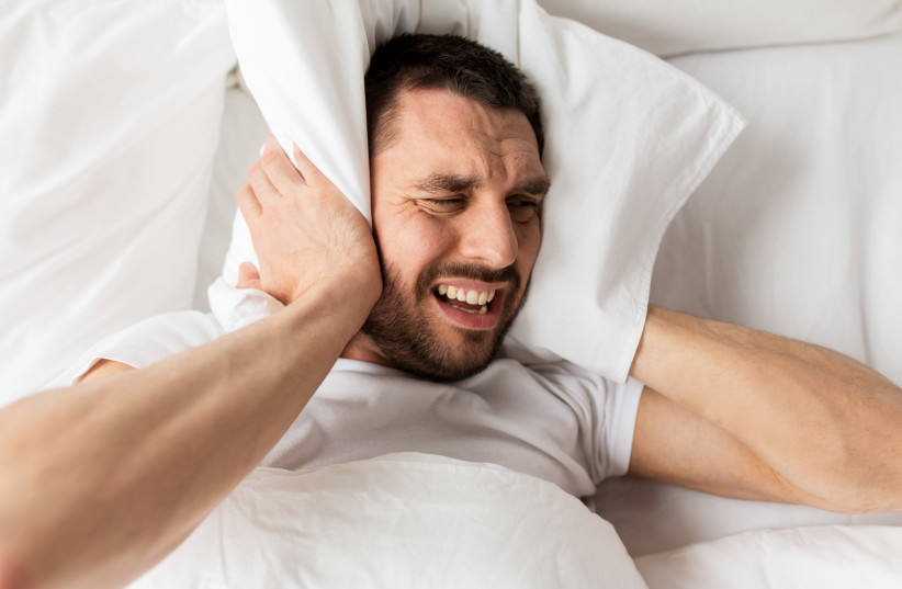 Man lying in bed with pillow suffering from noise  (photo credit: INGIMAGE)