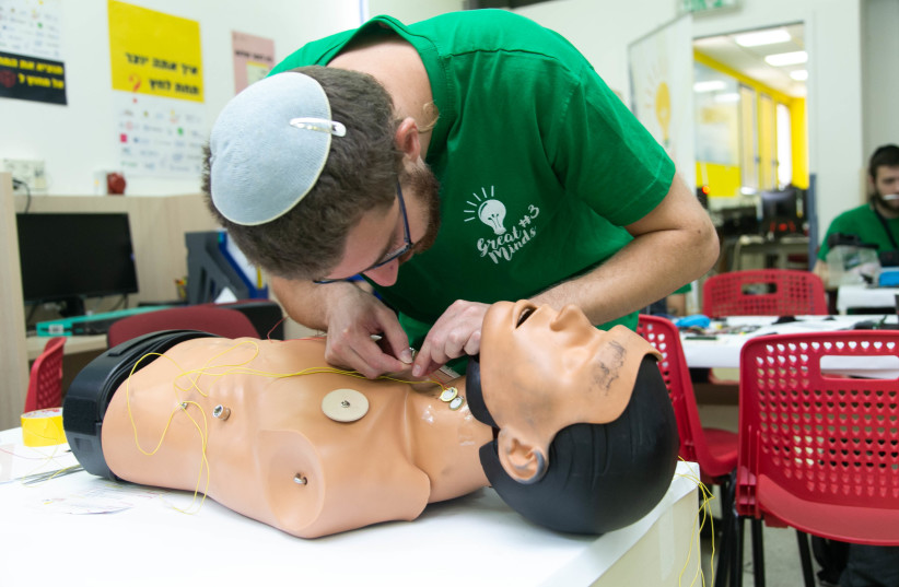 A Jerusalem College of Technology student workin on Magen David Adom training device at the annual Great Minds hackathon, May 2019 (photo credit: MICHAEL ERENBURG)