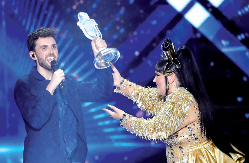 Duncan Laurence of the Netherlands accepts the Eurovision trophy from Israel's Netta Barzilai. (photo credit: RONEN ZVULUN / REUTERS)