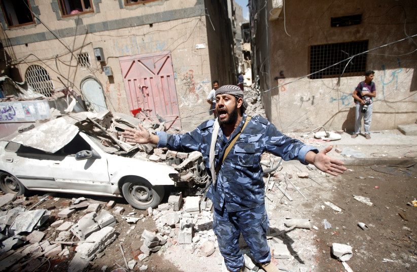 A Houthi security officer reacts at the site of an air strike launched by the Saudi-led coalition in Sanaa, Yemen May 16, 2019 (photo credit: REUTERS/MOHAMED AL-SAYAGHI)