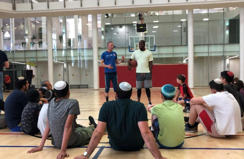 Basketball greats Tamir Goodman, left, and Michael Redd (right) conducting a basketball clinic for residents of World Emunah's Neve Landy Children's Village at the Jerusalem YMCA, May 2019 (photo credit: YAEL COHENCA)
