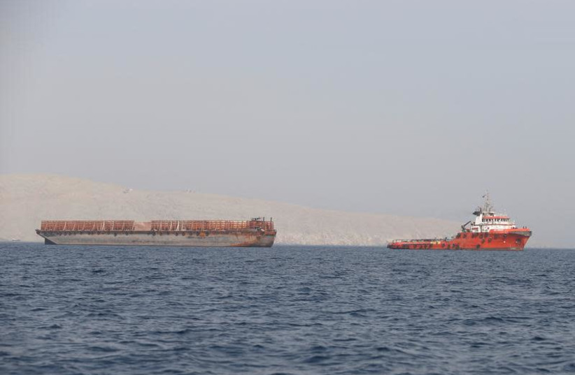 A tugboat moves cargo towards the Strait of Hormuz off the coast of Musandam province, Oman, July 20, 2018 (photo credit: HAMAD I MOHAMMED/REUTERS)