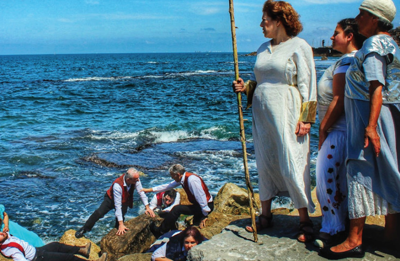 Key members of 'The Tempest' cast determinedly negotiate the jagged rocks of Jaffa's coastline: (From left) Michelle Adam, Talya Bem, Shimi Herman, Robin Stamler, Stephen Lerner, Yedidya Fraiman, Shlomit Kovalsky, Sandy Cash, Aliza Schoffman-Land, Sharon Benjamini. (photo credit: HANAN SCHOFFMAN)