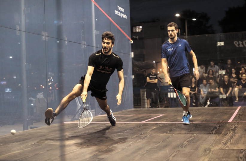 A pair of competitors take part in the professional squash tournament on Wednesday night in the outdoor glass court built in the center of Tel Aviv (photo credit: NIMROD ARONOV / COURTESY)