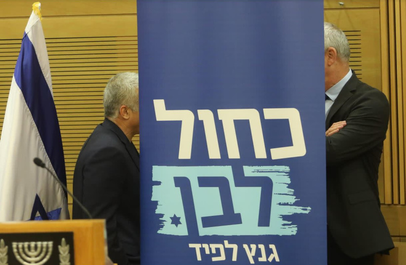 Blue and White leaders Benny Gantz (R) and Yair Lapid share words behind a party poster (photo credit: MARC ISRAEL SELLEM)