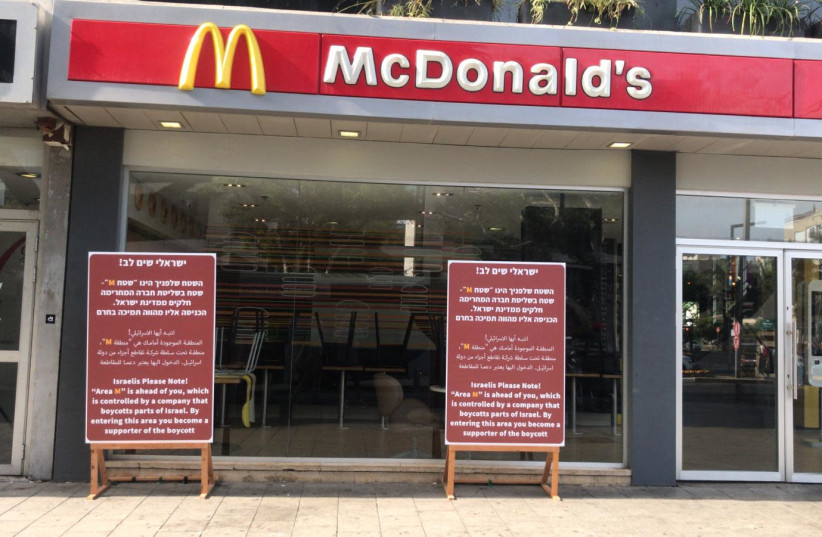 Signs outside a McDonald's in Tel Aviv protest the refusal of the local franchise to open in Judea and Samaria. (photo credit: MAARIV)