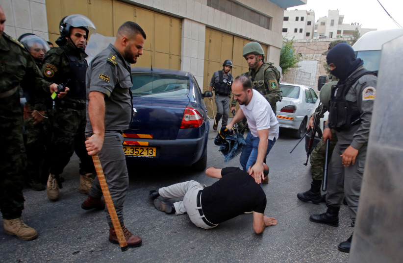 Palestinian Authority police prevent an end-of Ramadan prayer service by supporter of the Hizb-ut Tahrir in Hebron, June 4, 201 (photo credit: MUSSA QAWASMA / REUTERS)