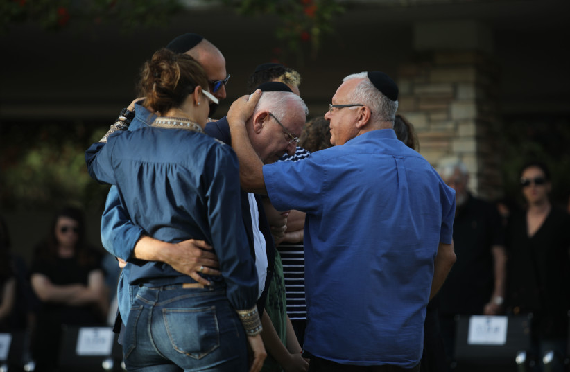 President Reuven Rivlin is comforted by family at his wife's funeral on Mt. Herzl, in Jerusalem, June 5, 2019 (photo credit: HADAS PARUSH/FLASH90)