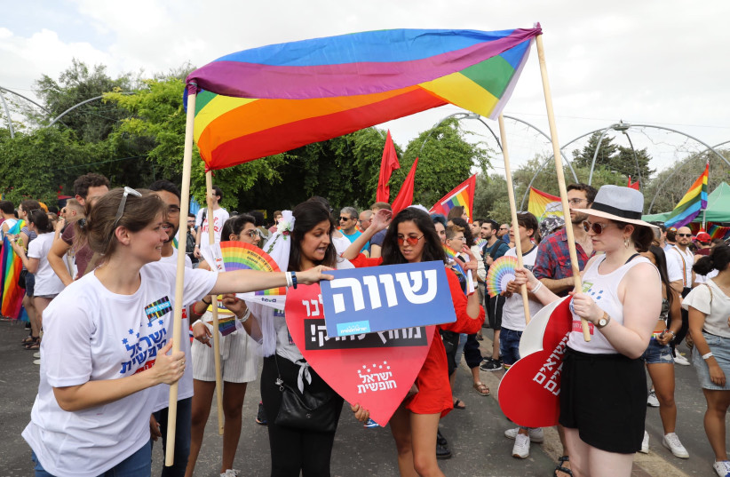 Jerusalem Pride parade attendees stand under a make-shift Chuppah made out of a Pride flag (photo credit: MARC ISRAEL SELLEM/THE JERUSALEM POST)