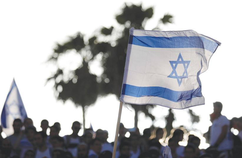AN ISRAELI flag held aloft on Jerusalem Day.  (photo credit: REUTERS)
