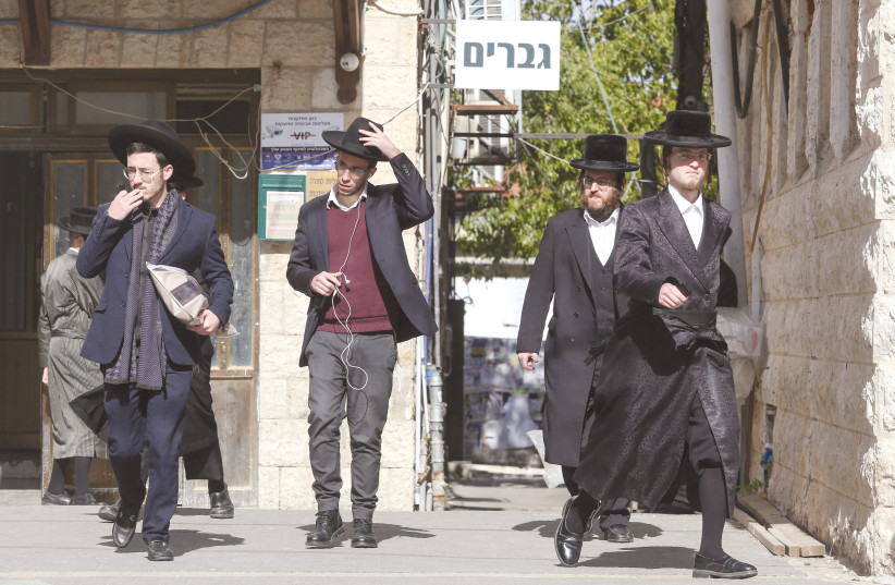 HAREDIM WALK in Jerusalem in front of a 'Men Only' sign – the role of religion in public life will likely increase due to demographic trends and the high birth rate in the haredi and national-religious sectors. (photo credit: MARC ISRAEL SELLEM/THE JERUSALEM POST)
