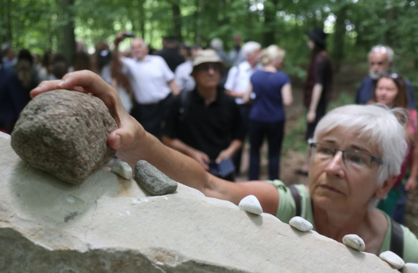 A local resident of the Polish town of Karminowice near Lublin places a stone to honor the memory of Jewish victims of the Holocaust  (photo credit: STEVEN D. REECE/ THE MATZECAH FOUNDATION)