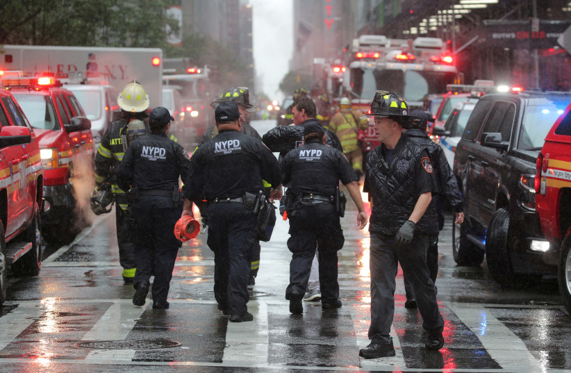New York City police and firefighters arrive at the scene after a helicopter crashed atop a building in Times Square and caused a fire on the roof in the Manhattan borough of New York, New York, U.S., June 10, 2019. (photo credit: BRENDAN MCDERMID/REUTERS)