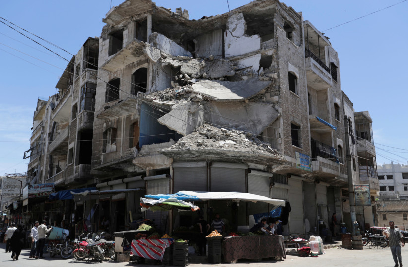 People walk past a damaged building in the city of Idlib on May 31, 2019. (photo credit: KHALIL ASHAWI / REUTERS)
