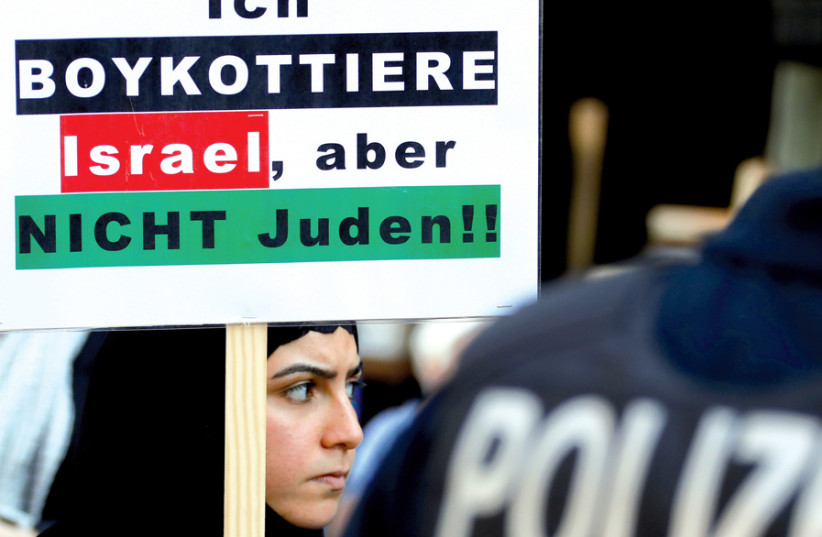 A protester holds a placard reading 'I boycott Israel, but not the Jews,' during a demonstration marking al-Quds Day (Jerusalem Day), in Berlin on June 1 (photo credit: FABRIZIO BENSCH / REUTERS)