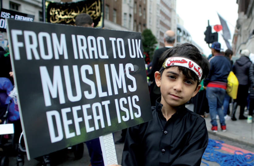 A boy holds a protest banner during an anti-ISIS march in central London (photo credit: TOM JACOBS/REUTERS)