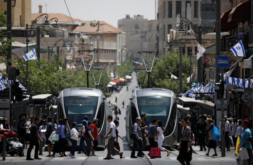 Pedestrians cross a street next to the light rail trams in Jerusalem May 11, 2017. Picture taken May 11, 2017.  (photo credit: REUTERS/AMIR COHEN)