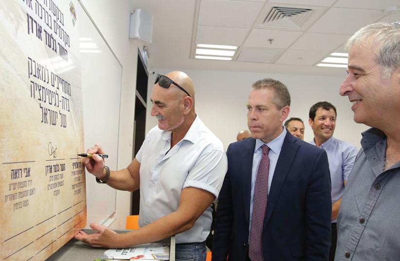 DAVID ELHAIINI, head of the Jordan Valley Regional Council, signs a resolution to fight BDS as Public Security Minister Gilad Erdan looks on. (photo credit: MIRI TZACHI)