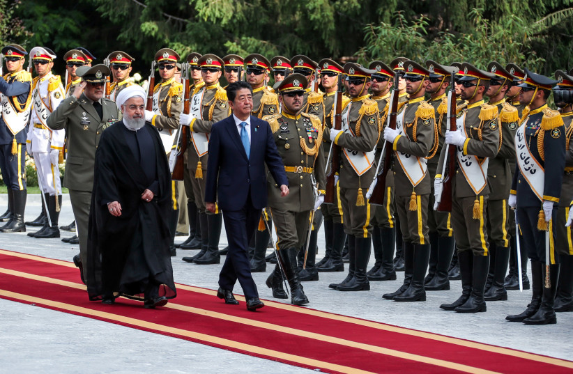 Iranian President Hassan Rouhani walks with Japan's Prime Minister Shinzo Abe, during a welcome ceremony in Tehran, Iran, June 12, 2019. (photo credit: REUTERS)