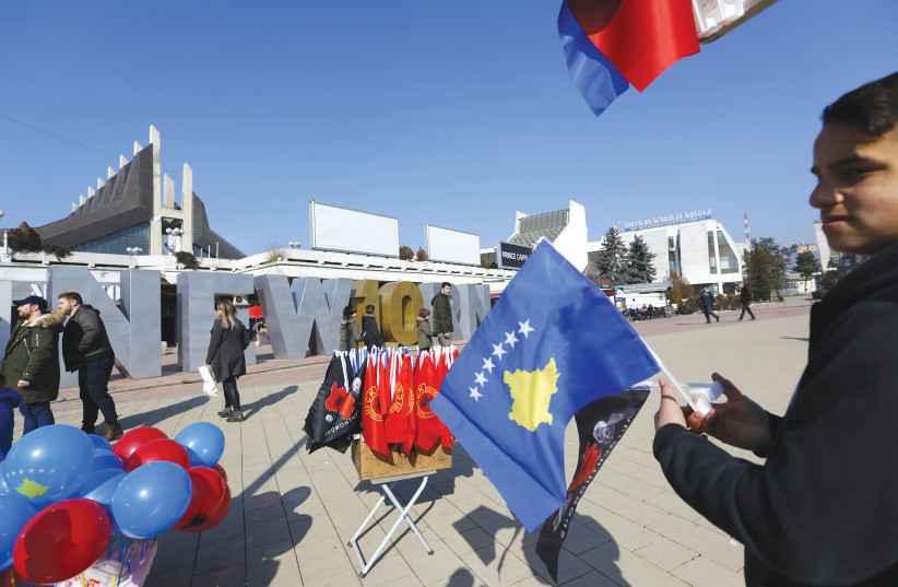A MAN holds a Kosovo flag (photo credit: REUTERS)